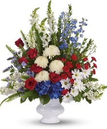 Red, white and blue flowers arranged in a white urn.
