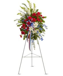 Patriotic sympathy arrangement of red, white and blue flowers with ribbon and greenery.