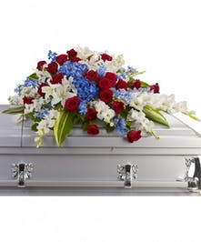 Patriotic casket spray of red, white and blue flowers and greenery.