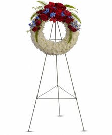 White floral wreath accented with red and blue flowers on an easel.