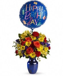 Colorful birthday bouquet of flowers inside a blue vase with a happy birthday balloon