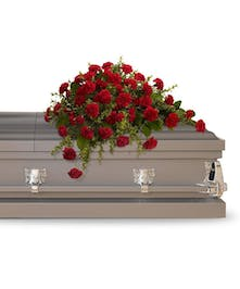 Casket spray of red carnations and mini carnations accented with greenery.
