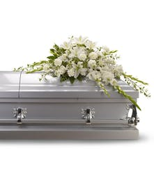 Casket spray made of all white flowers and simple greenery.