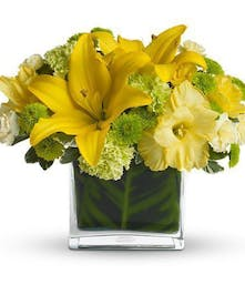 Yellow liliws and green flowers in a glass cube vase.