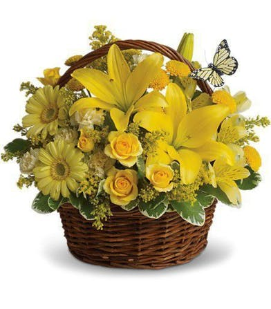 Yellow lilies, roses and daisies in a woven handbasket with butterfly decoration.