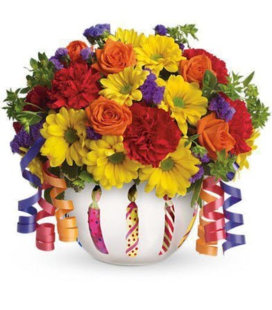 Bright flowers in a frosted glass bowl vase adorned with a shiny birthday candle motif.