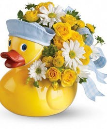 Vase that looks like a rubber duck holidng yellow and white flowers with a blue ribbon.