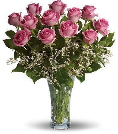 One dozen pink roses in a clear glass vase.