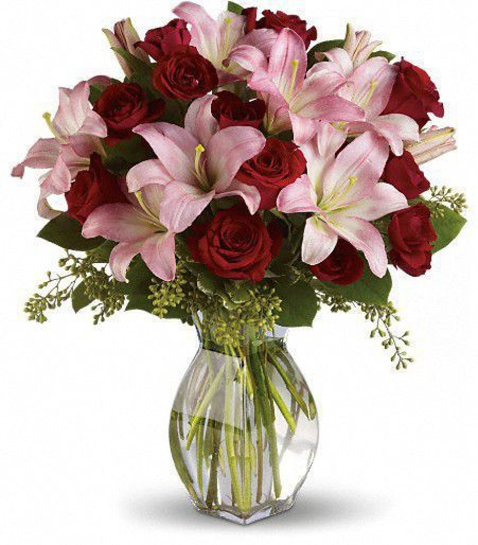 Red roses & pink lilies in a clear glass vase.