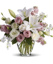 Light pink and white roses, lilies, lisianthius, sweet pea, and pink stock in a clear glass vase.