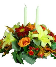 Red, gold and orange flowers in a centerpiece arrangement.