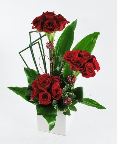Modern arrangement of red roses in a glass vase.