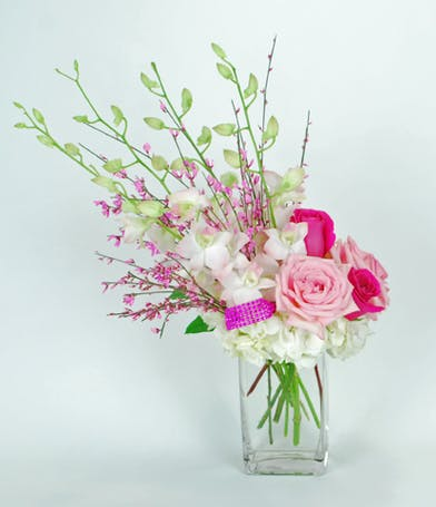 Blush orchids, hydrangea and pink roses in a clear glass vase.