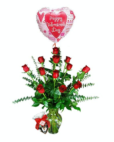 One dozen red roses in a clear glass vase, with a box of chocolates and balloon that says Happy Valentine's Day.
