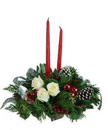 Greenery, white flowers and pinecones with two red candles in the middle of the centerpiece.